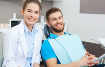 A dentist and a relaxed satisfied man in a dental chair after wisdom tooth removal procedure.