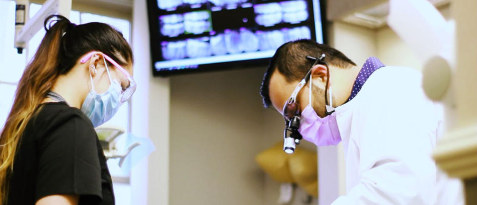A dentist with an assistant during a procedure.