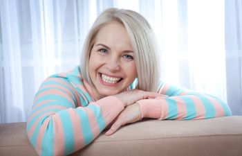 A broadly smiling woman happy with her new dentures Marietta GA