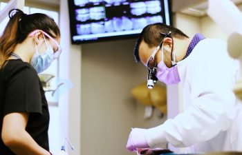 Pure Smiles Dentistry dentist and his assistant performing dental treatment.