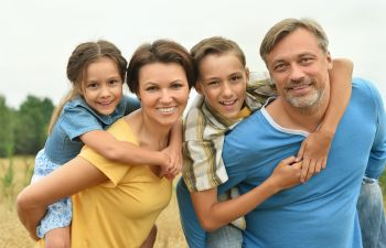 A broadly smiling family of four