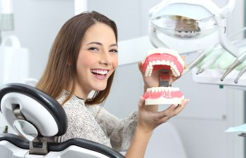 A smiling woman in a dentist chair presenting teeth and gums model