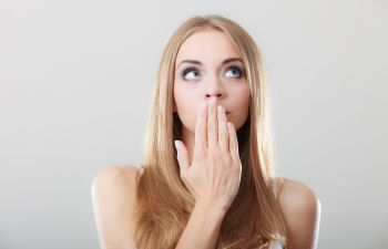 A woman covering her mouth because of halitosis.