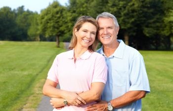 An elderly couple with perfect smiles after implant restoration Marietta GA