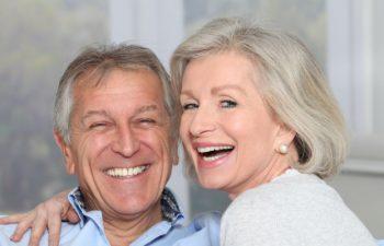 A broadly smiling elderly couple after dental implant restoration Marietta GA