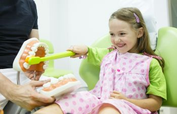 A pre-school girl in a dental chair being educated about oral health at Marietta GA dentistry.