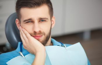 A man with tooth pain in a dentist chair before root canal treatment Marietta GA