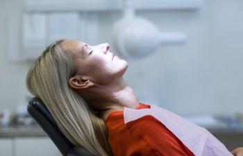 A woman in a dentist chair under dental sedation Marietta GA