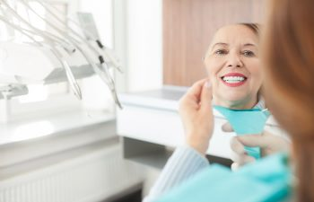 A mature woman after dental restorative treatment looking at her teeth in the mirror.