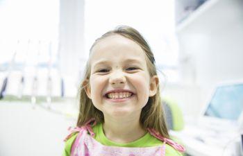 A broadly smiling pre-school girl in a dentist office Marietta GA