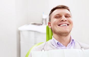 A broadly smiling man in a dentist chair Marietta GA