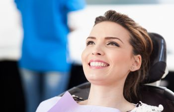 A relaxed woman with beautiful teeth in a dentist chair during cosmetic treatment in Marietta GA.