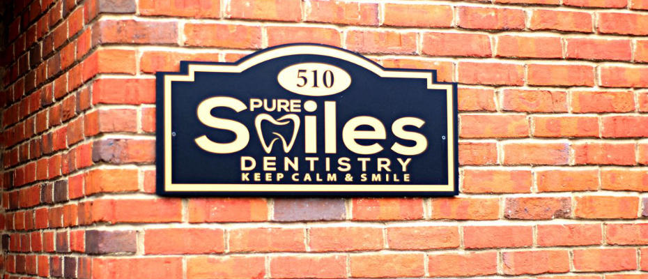 sign on a wall with the pure smiles dentisty logo