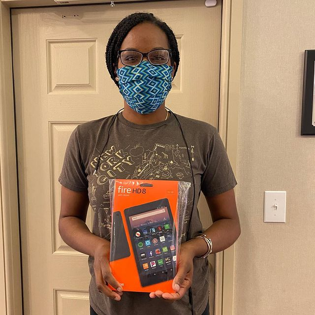 African-American girl with a mask on her face holding a box with a tablet